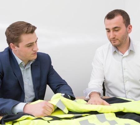 Zwei Mitarbeiter von ProGARM prüfen die Kleidungsstücke